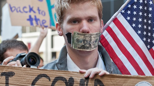 """I could lose my job for having a voice."" A dollar bill was taped over the mouth of the sign carrier but the young man spoke volumes. Silence those who speak truth to power."